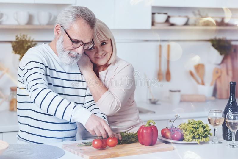 Positive lovign aged couple standing in the kitchen royalty free stock images