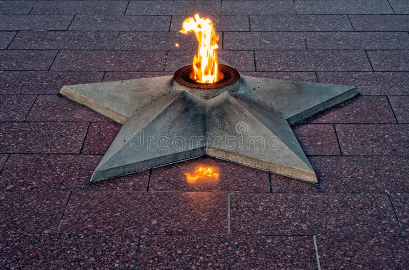 An eternal flame at a war memorial. Eternal flame that commemorates the dead of the Second World War is a symbol of sacrifice and of the eternity of remembrance stock images