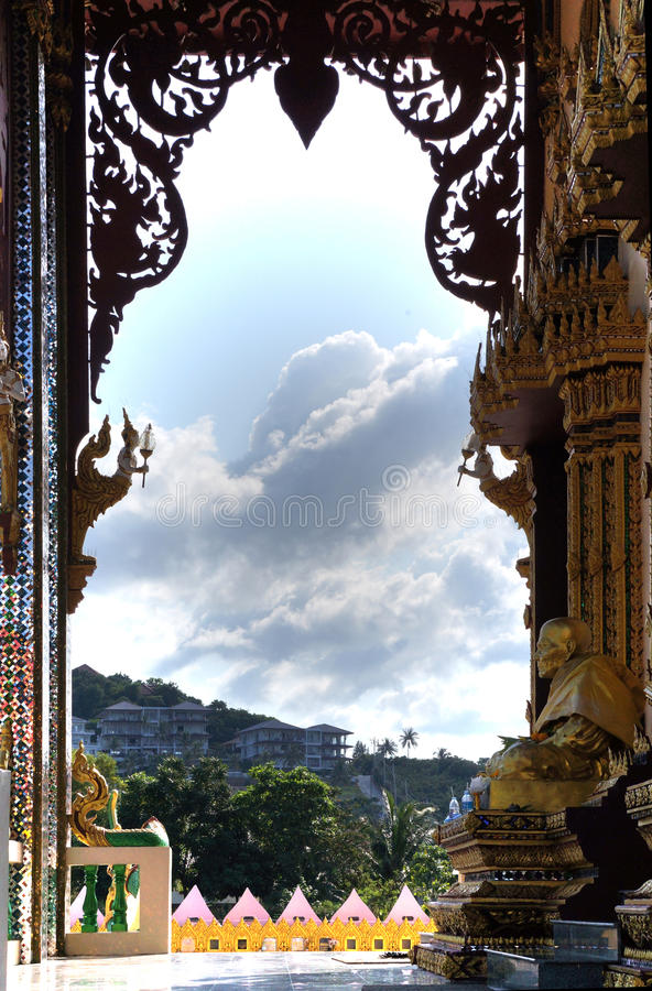 Eternity passes ... Statue of a seated monk in a Buddhist temple Wat Laem Suvannaram. Flying clouds and expensive villas in the distance on a hillside stock images