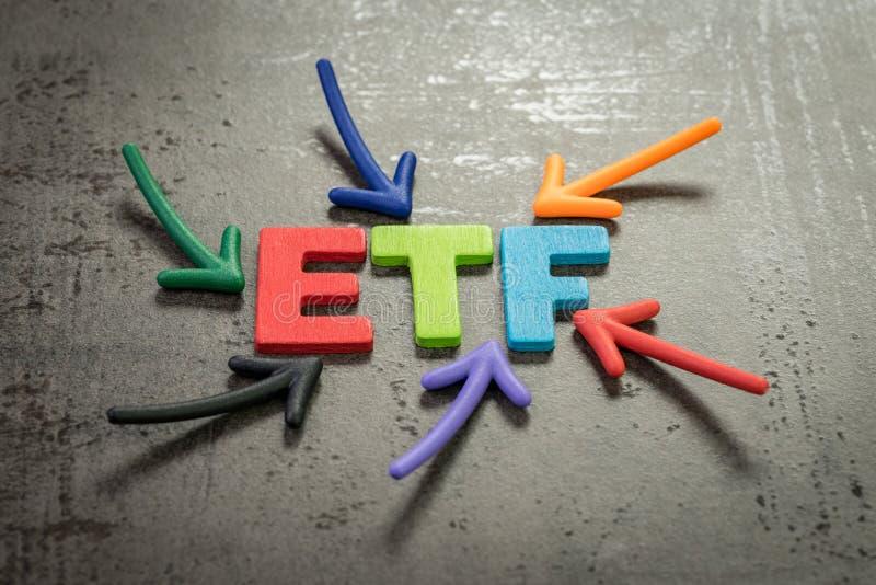 ETF utbyte-handlad fond en investeringsfond som handlas på börsbegrepp, mång- färgpilar som pekar till ordet ETF på arkivfoto