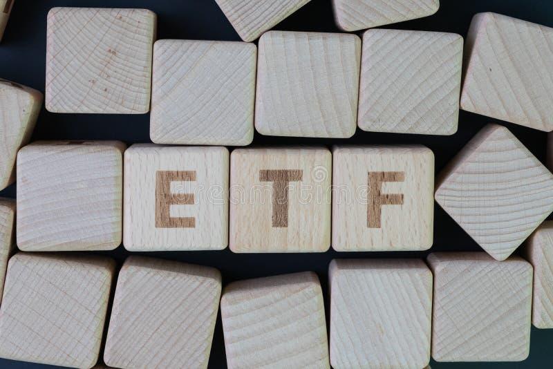 ETF, Wekslowy Handlujący funduszu pojęcie, sześcianu drewniany blok z abecadłem buduje słowo ETF przy centrum na ciemnym blackboa zdjęcia royalty free
