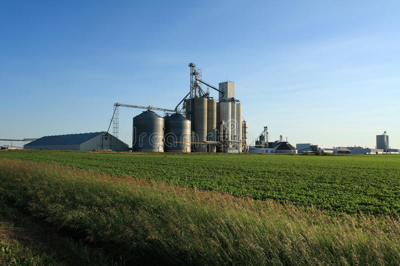 Ethanol is Grown. An ethanol plant in Iowa with a soybean field in the foreground stock photo