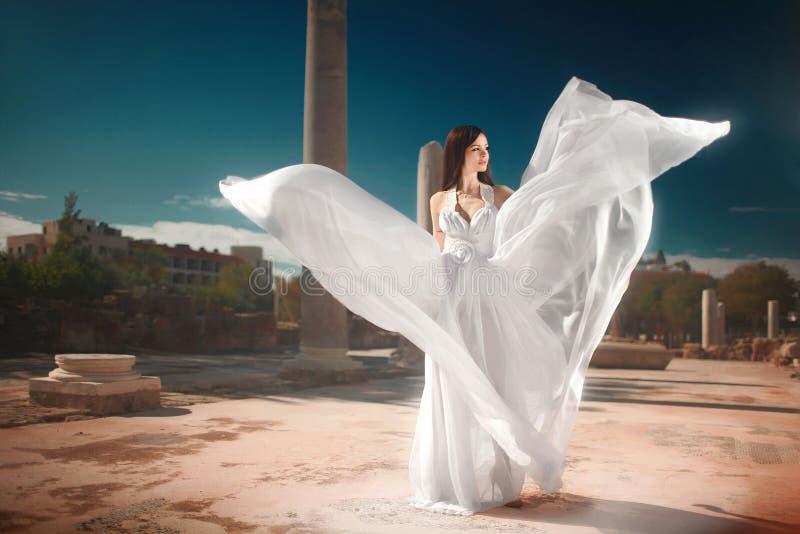 Ethereal, θεία νύφη με το πέταγμα, λαμπρό φόρεμα που στέκεται temp στοκ εικόνα