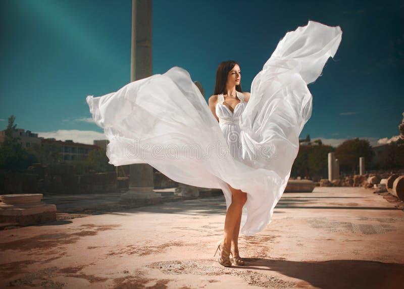 Ethereal, θεία νύφη με το πέταγμα, λαμπρό φόρεμα που στέκεται temp στοκ εικόνα με δικαίωμα ελεύθερης χρήσης