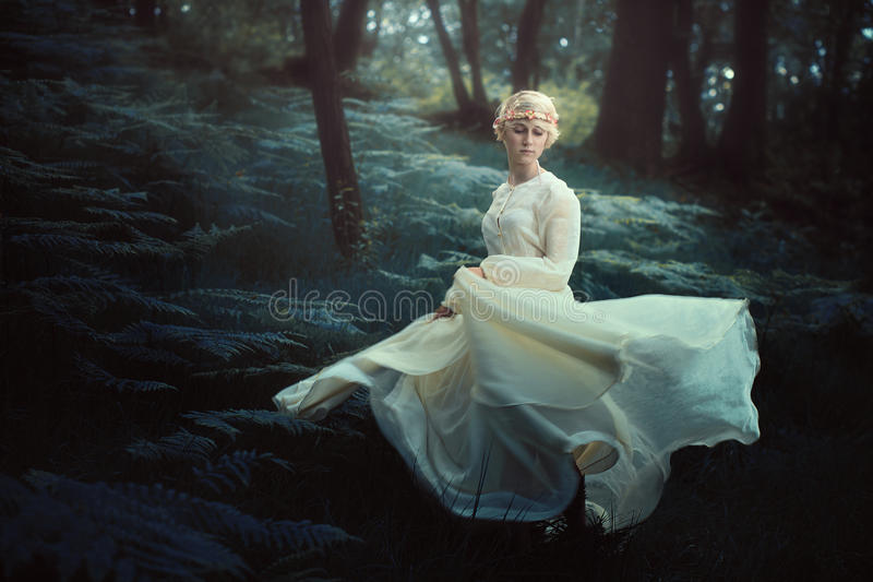 Ethereal woman dancing in dreamy forest stock image