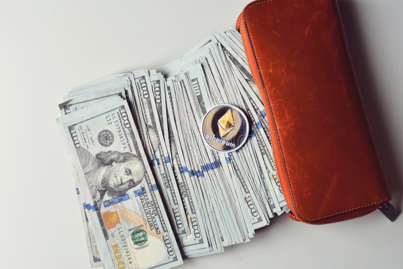 Ethereum auf Stapel von US-Dollar Rechnungen, Hälfte innerhalb einer orange Geldbörse stockfotografie