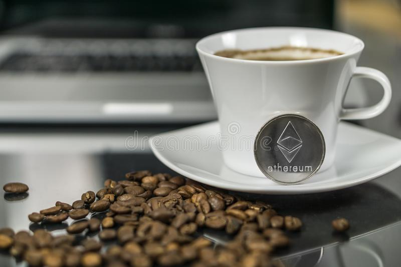Ethereum cryptocurrency coin with coffee cup and coffee beans royalty free stock images