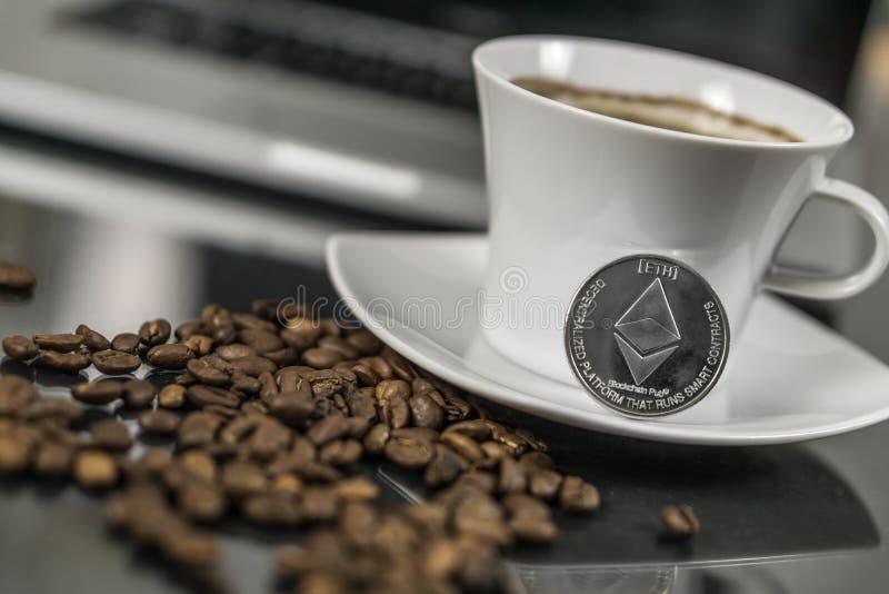 Ethereum cryptocurrency moneta z filiżanką i kawowymi fasolami zdjęcie royalty free