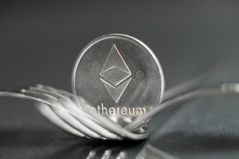 Ethereum cryptocurreny mynt som förläggas mellan gafflar med reflexion, hård gaffel fotografering för bildbyråer