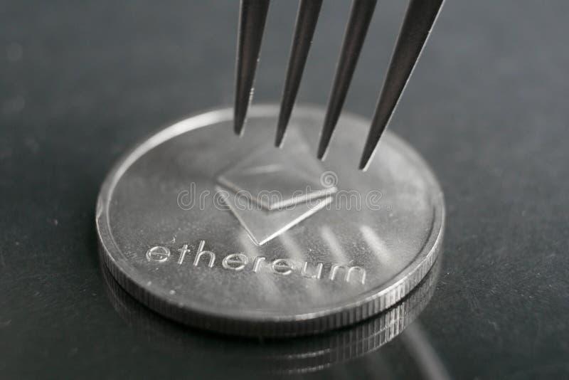 Ethereum cryptocurreny mynt som förläggas mellan gafflar med reflexion, hård gaffel royaltyfri foto