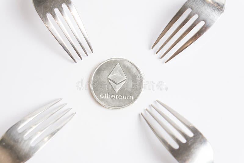 Ethereum cryptocurreny silvermynt som förläggas mellan gafflar på vit bakgrund, hård gaffel arkivbilder