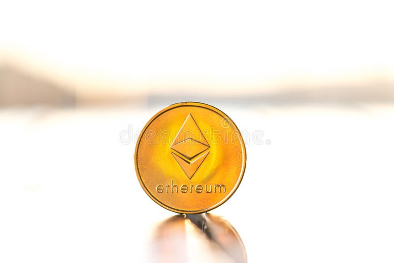 Ethereum guld- färgmynt med solnedgångvitbakgrund Cryptocurrency faktiskt mynt arkivfoto