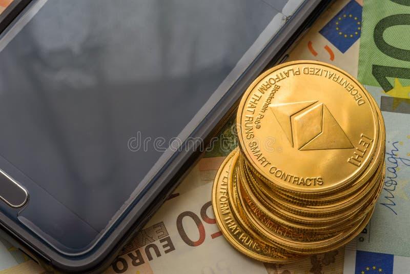 Ethereum monety brogować na euro notatkach obok smartphone, przyszłościowego pojęcia pieniężna waluta, crypto waluta znak fotografia royalty free