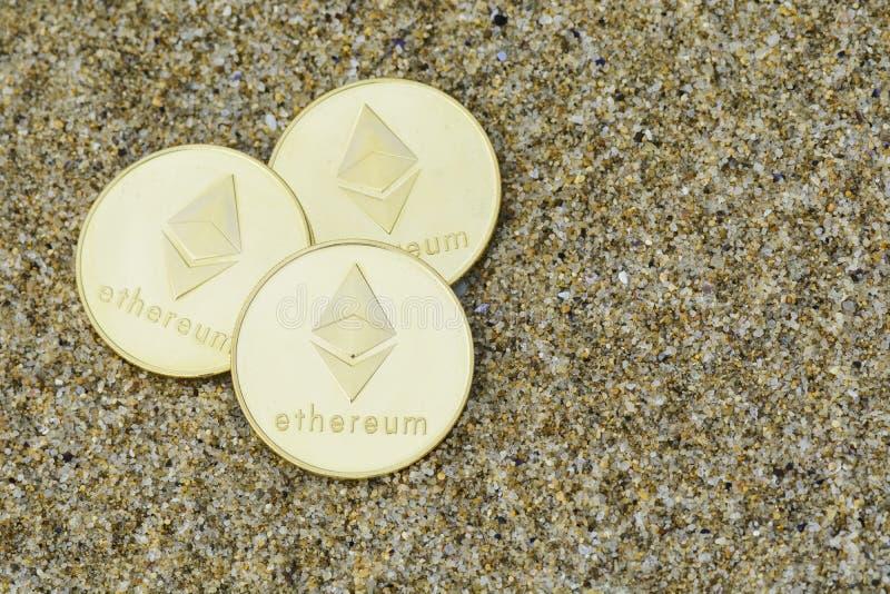 Ethereum myntslut upp på stranden, guld- färg royaltyfri bild