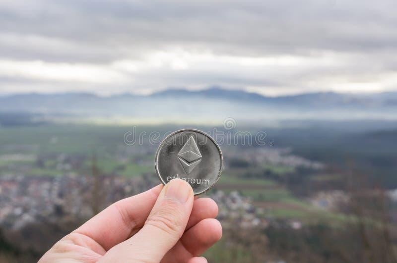 Ethereum srebna moneta, ręka chwyt Ethereum nad miasto zdjęcia royalty free