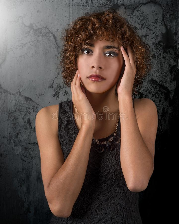 Etherische mooie gemengde ras jonge vrouw met verbazende ogen en krullend haar stock fotografie