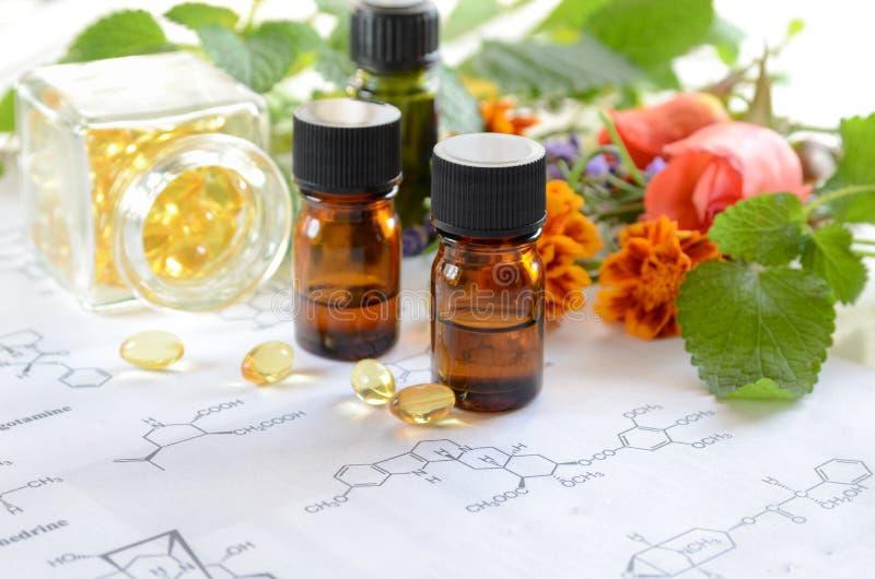 Etherische oliën met kruiden en supplement op wetenschapsblad royalty-vrije stock afbeelding
