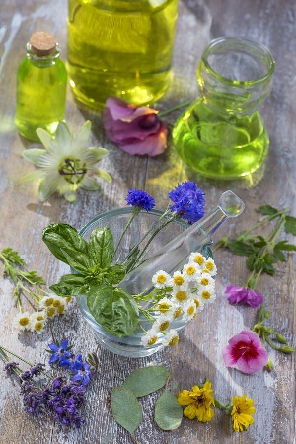 Etherische oliën voor aromatherapy behandeling met verse kruiden op mortier witte achtergrond stock foto's