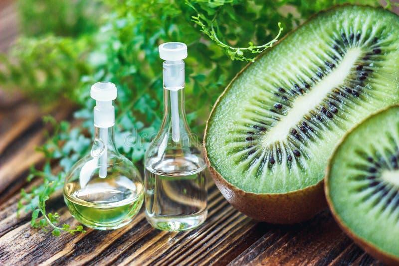 Etherische olie in glasfles met vers, sappig kiwifruit en groene blad-schoonheid behandeling Zeep, handdoek en bloemensneeuwklokj royalty-vrije stock foto