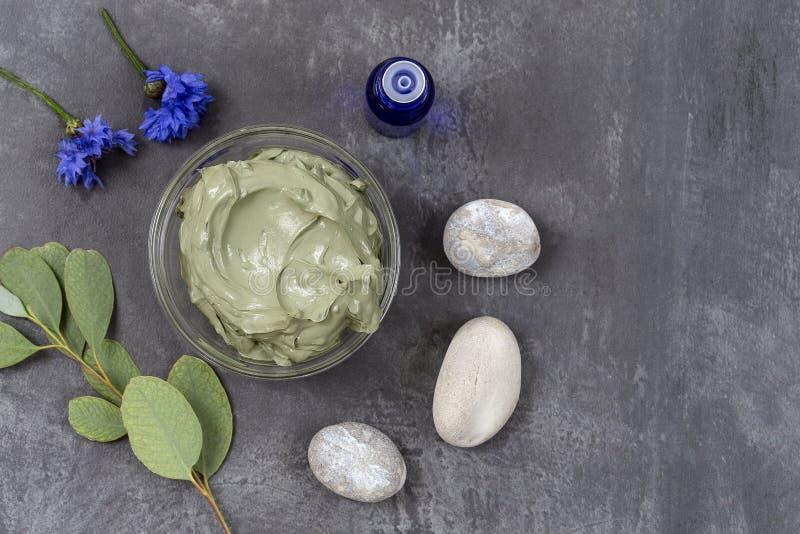 Etherische olie met kosmetische klei en bloem en tak van eucalyptus, stenen, voor kuuroordbehandelingen, in glaskom op grijs royalty-vrije stock foto