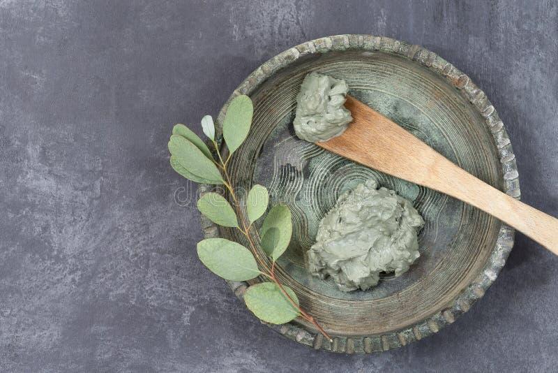 Etherische olie met kosmetische klei en korenbloem en tak van eucalyptus, stenen, voor kuuroordbehandelingen, in houten lepel,  stock fotografie