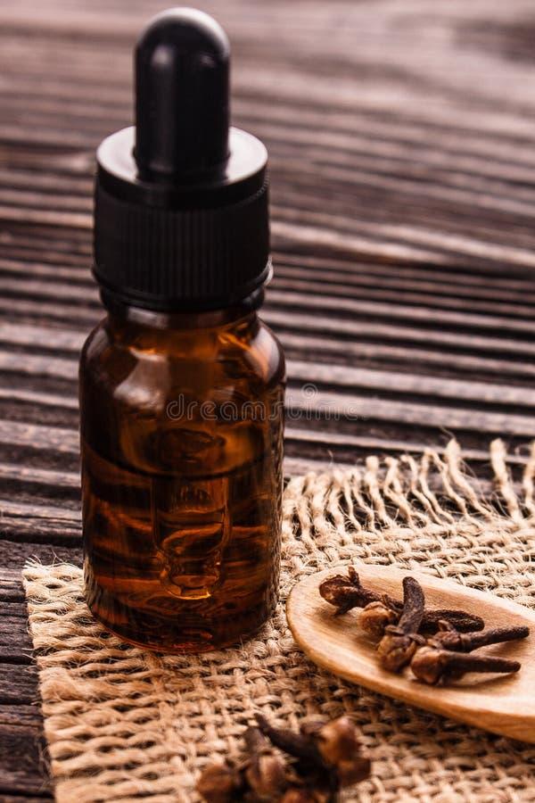 Etherische olie van kruidnagels op een houten rustieke achtergrond royalty-vrije stock foto