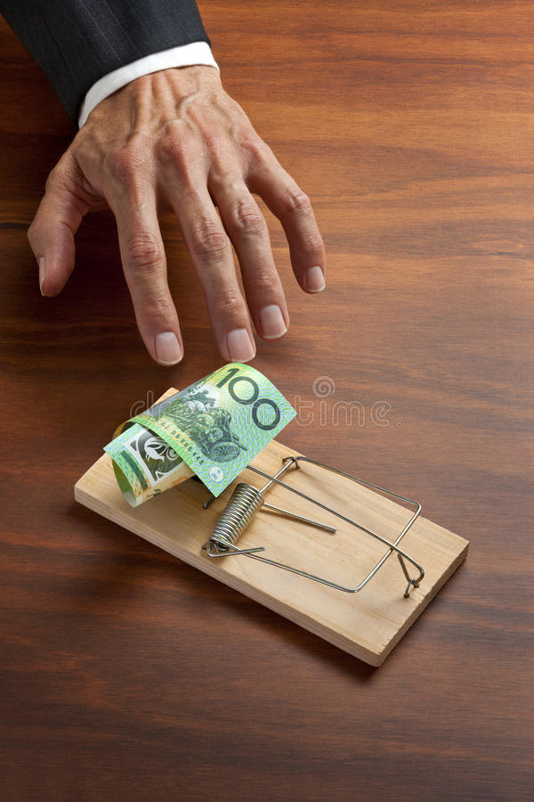 Australian Money Ethics Business. A conceptual image of a businessmans hand reaching in to grab an Australian money set in a mouse or rat trap stock images