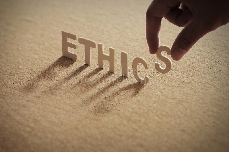 ETHICS wood word. On compressed board with human`s finger at S letter royalty free stock photography