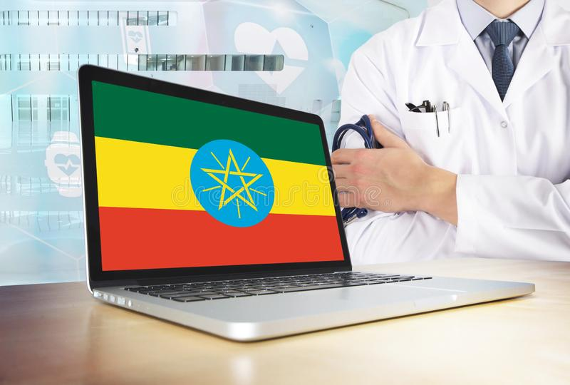 Ethiopia healthcare system in tech theme. Ethiopian flag on computer screen. Doctor standing with stethoscope in hospital. Cryptocurrency and Blockchain royalty free stock photo