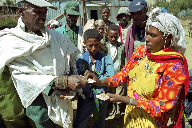 Ethiopian farmer receives money for sale corn. Ethiopia, Sululta district, Mulo village, Oromo female small farmer, largest Ethiopian ethnic group, in colorful royalty free stock images