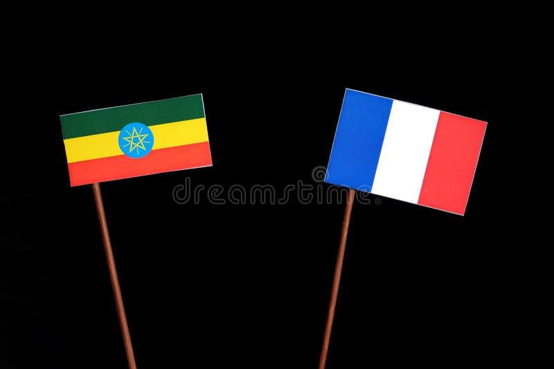 Ethiopian flag with French flag isolated on black. Background stock photos