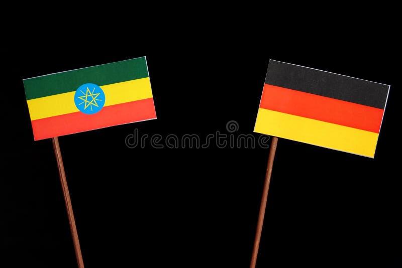 Ethiopian flag with German flag isolated on black. Background stock photo