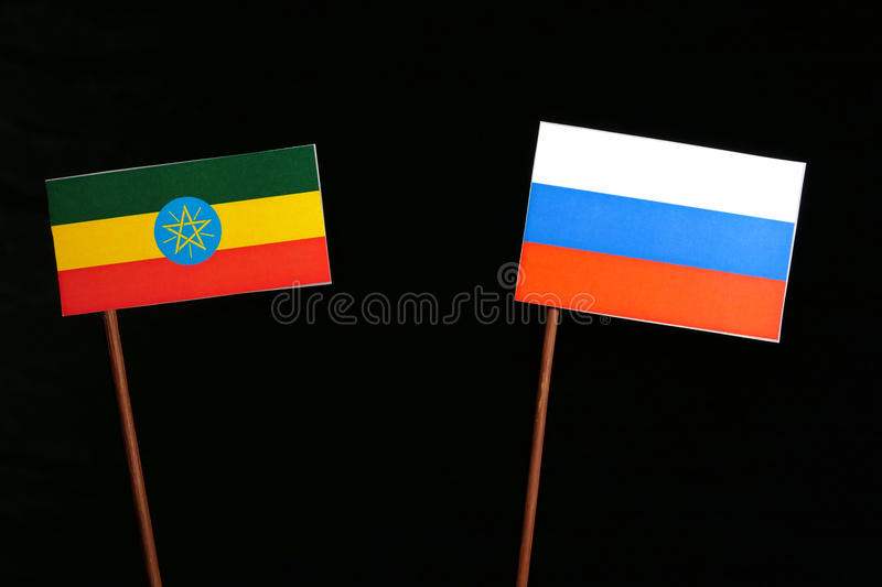 Ethiopian flag with Russian flag isolated on black. Background stock image