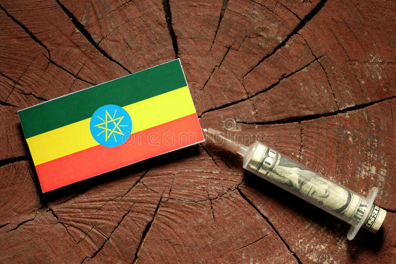 Ethiopian flag on a stump with syringe injecting money. In flag stock photos