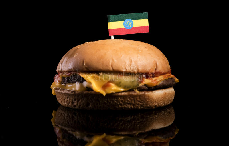 Ethiopian flag on top of hamburger isolated on black. Background royalty free stock photo