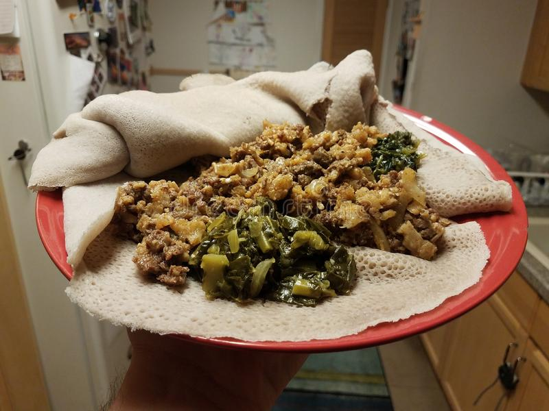 Ethiopian food beef and tripe with greens and bread. On red plate in kitchen royalty free stock photography