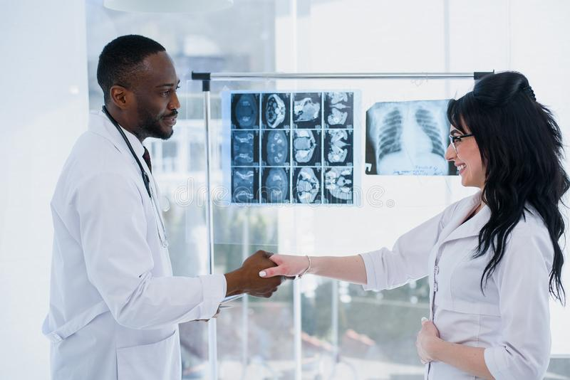 Ethiopian male and caucasian female doctors at hospital shaking hands. Medical workers greeting each other. Concept of royalty free stock photos