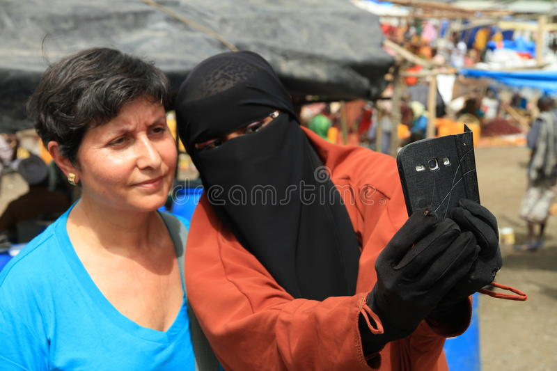 Ethiopian woman with burka is making a selfie with a tourist royalty free stock photography