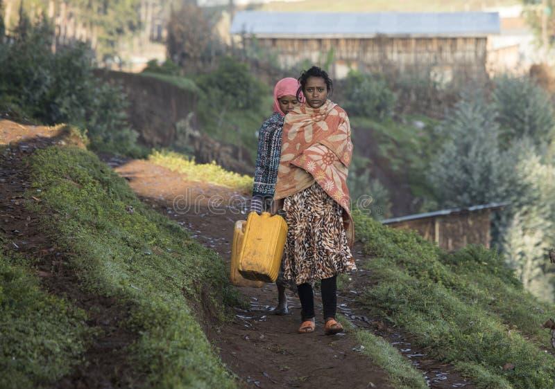Ethiopian women carrying water jugs royalty free stock photos