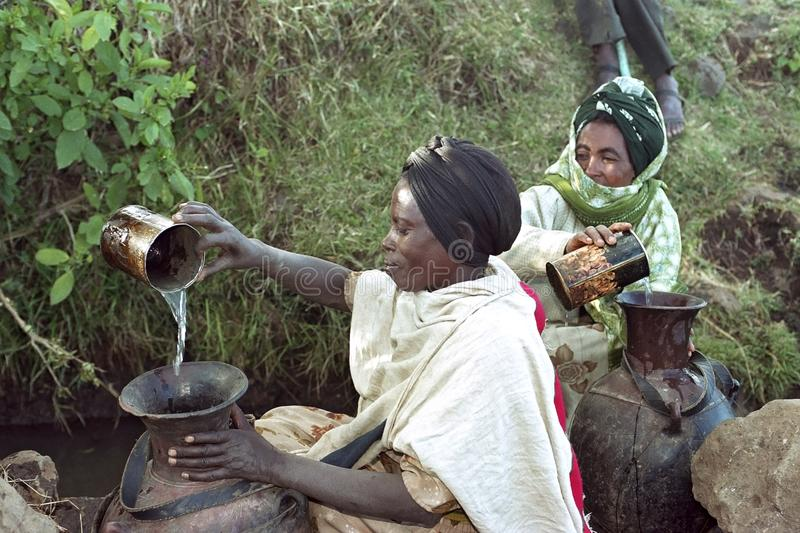 Ethiopian women fetch water from natural well. Ethiopia: Village CHANCHO Gaba Robi: by the Oromia, the largest ethnic group in Ethiopia, in the Highlands, Water royalty free stock photography