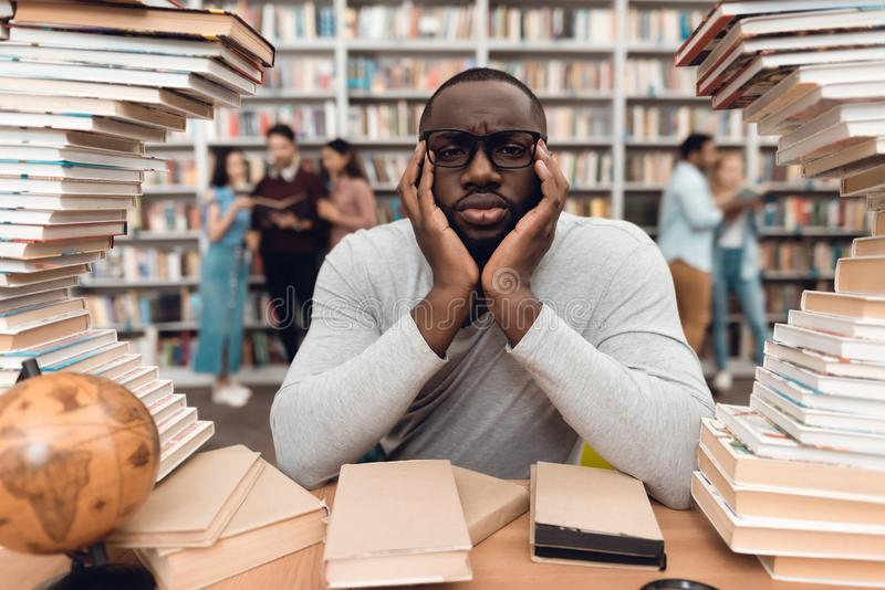 Ethnic african american guy surrounded by books in library. Student is bored and tired. royalty free stock photos