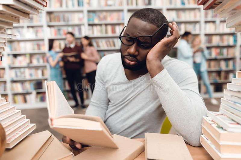 Ethnic african american guy surrounded by books in library. Student is bored and tired. stock image