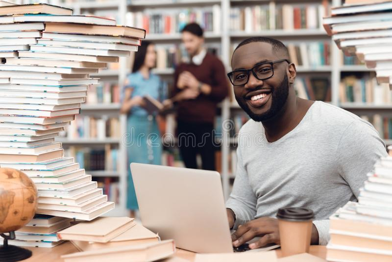 Ethnic african american guy surrounded by books in library. Student is using laptop and drinking coffee. stock image