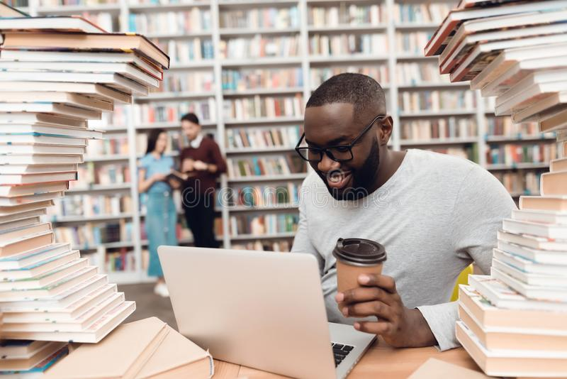 Ethnic african american guy surrounded by books in library. Student is using laptop and drinking coffee. stock images
