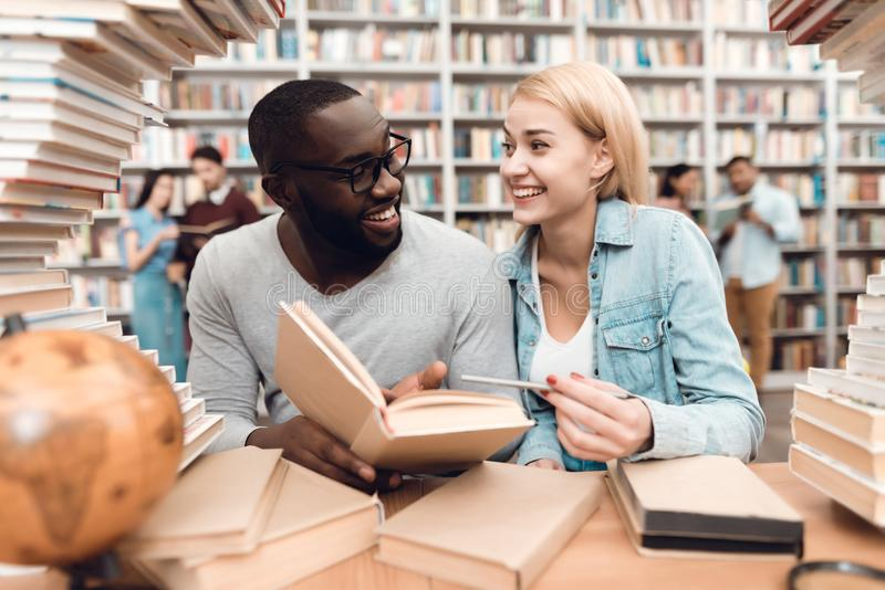 Ethnic african american guy and white girl surrounded by books in library. Students are reading book. stock images