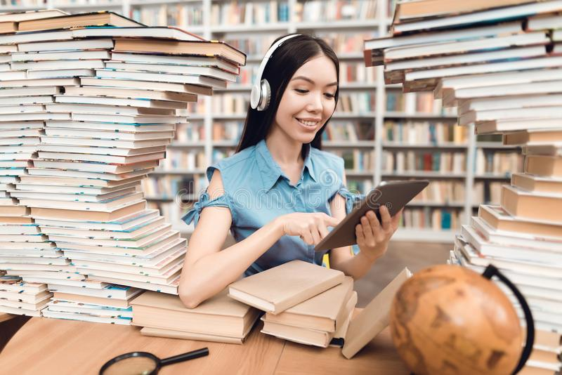 Ethnic asian girl surrounded by books in library. Student is using tablet. stock images