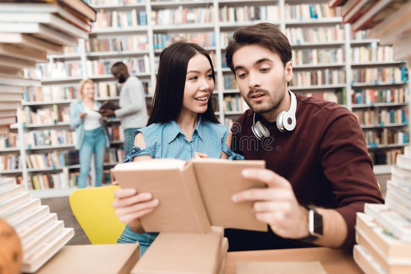 Ethnic asian girl and white guy surrounded by books in library. Students are reading book. royalty free stock photos