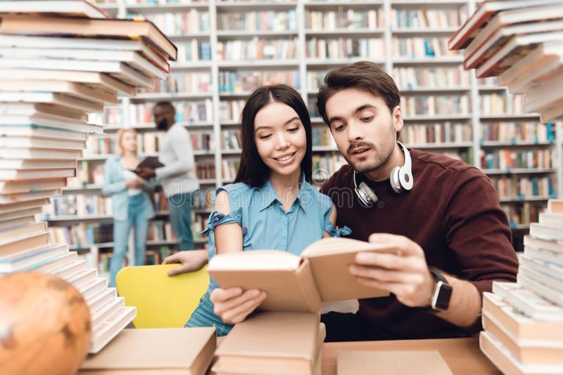 Ethnic asian girl and white guy surrounded by books in library. Students are reading book. stock photos
