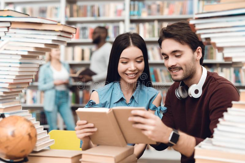 Ethnic asian girl and white guy surrounded by books in library. Students are reading book. stock photo