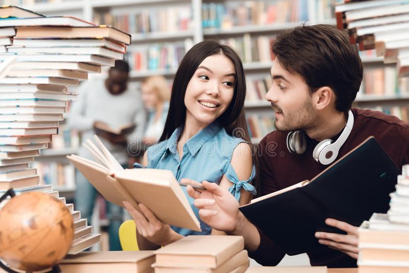 Ethnic asian girl and white guy surrounded by books in library. Students are reading books. royalty free stock photo